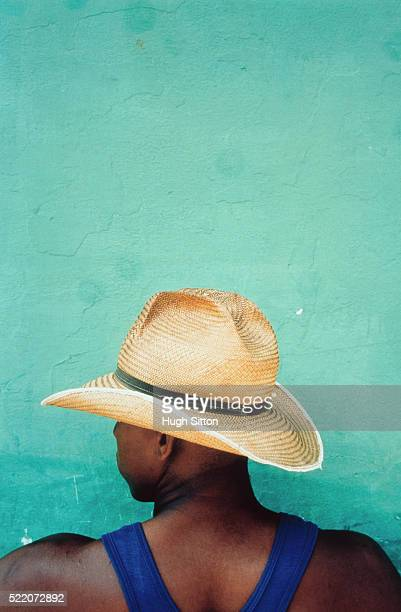 cuban wearing straw hat in front of green wall - hugh sitton stockfoto's en -beelden