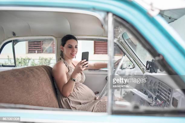 Femme cubaine vérification téléphone mobile sur sa voiture
