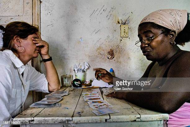 Cuban woman consults her health problem with a fortune teller, practitioner of a Afro-Cuban religion, in Santiago de Cuba, Cuba, August 4, 2008. The...