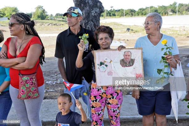 Cuban woman holds a photo of late Cuban Revolution leader Fidel Castro during a march from the Revolution square to the Santa Ifigenia cemetery as...