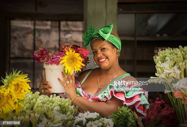 Cuban woman in a traditional dress selling flowers