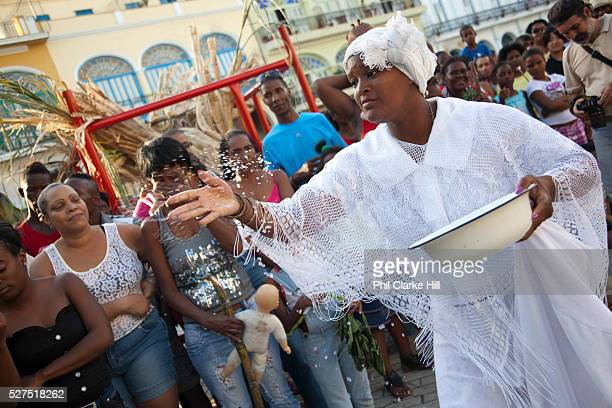 Cuban woman of African descent throwing rice to the crowd in a traditional gesture Performance in Havana old town local dance and theatre group...
