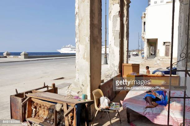 Cuban woman rests on her bed outside her partly destroyed apartment as the MS Opera cruise ship leaves Havana at the Malecon waterfront after...