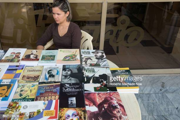 Cuban woman selling books in the porch of a bookstore Books are displayed on table various genre literary works for sale