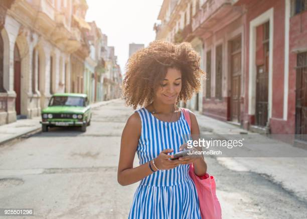 Cuban woman sends text message on phone in street
