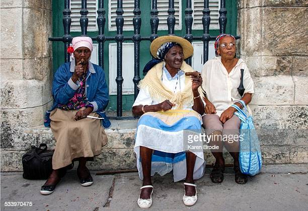 A Cuban woman smokes her cigar while sitting on a window sill and socializing with her two friends in Old Havana Cuba