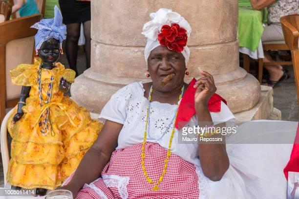 cuban woman smoking a cigar at old havana street, cuba. - cuban doll stock pictures, royalty-free photos & images