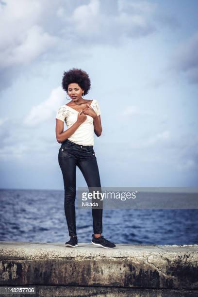 cuban woman standing on the malecon seawall, havana, cuba - afro caribbean ethnicity stock pictures, royalty-free photos & images