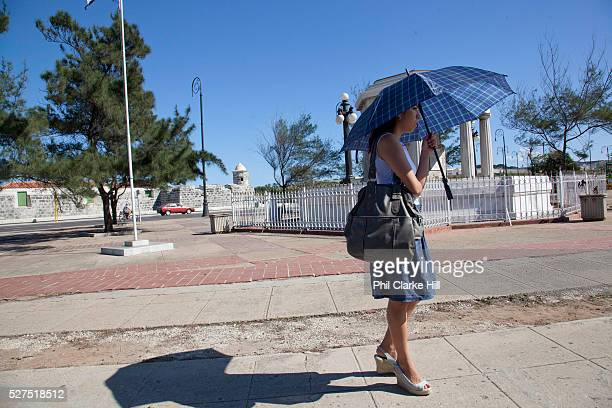 Cuban woman standing on the street waiting for a taxi bus using an umbrella to shade herself from the sun Havana