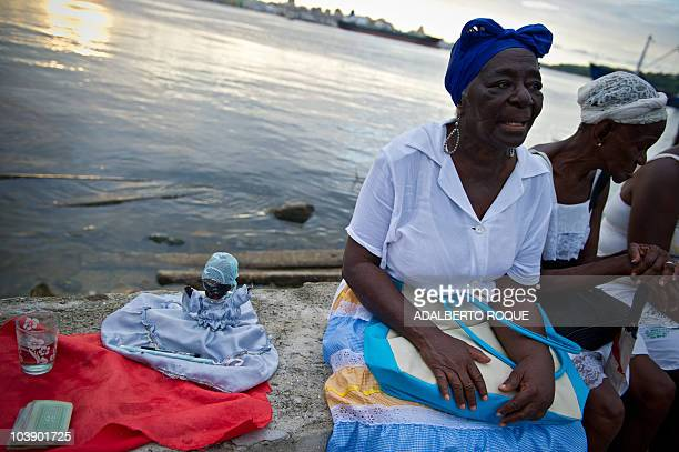Cuban women wait for the celebrations of the Yemaya Day next to a doll representing the Yemaya Goddess of the Yoruba religion in the waterfront of...