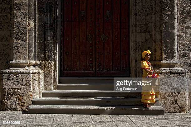 Cuban women waiting at the door steps of Havana Cathedral wearing the traditional Cuban style dressin yellow