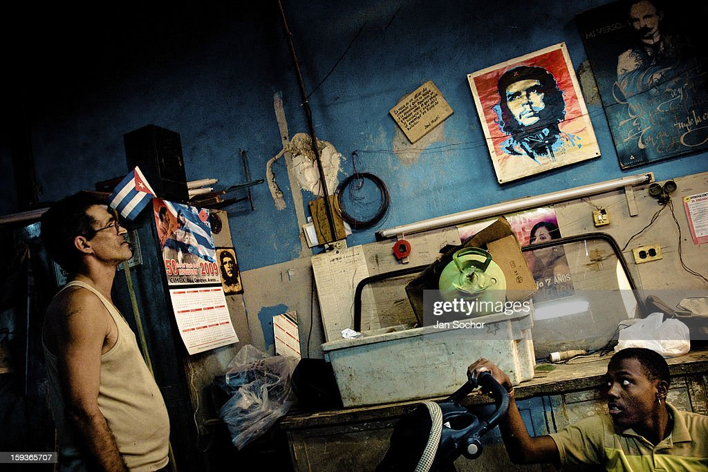 A Cuban worker watches an iconic portrait of the revolutionary leader Che Guevara, hung on the wall of a working room, in Havana, Cuba, 11 February 2009 in Havana, Cuba. During the Cuban Revolution, an armed rebellion at the end of the 1950s, most of the revolutionary leaders started as unnamed soldiers fighting from the jungle. After taking over the power, they became autocratic rulers holding almost absolute power and pursuing the opposition. For some reason Cuban people never stopped to worship Fidel Castro, Che Guevara, Raul Castro and others. Cubans hang their photos and portraits on the wall at home, shops and working places even when they don't have to.