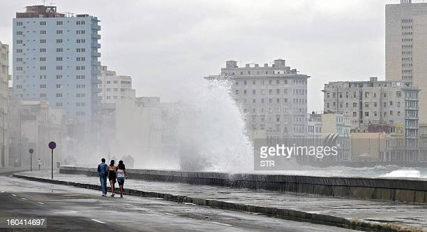 Cuban youngsters walk while a giant wave hits the seafront in Havana on November 16 2008 A cold front that affects Cuba is causing giant waves AFP...