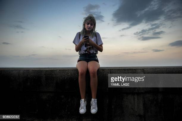 A Cuban youtuber checks her cellphone at Havana's Malecon on February 27 2018 Cubans don't have internet access at their homes yet the telephone...