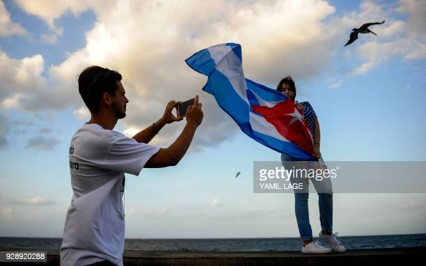 A Cuban youtuber poses for a picture with the Cuban flag at Havana's Malecon on February 27 2018 Cubans don't have internet access at their homes yet...