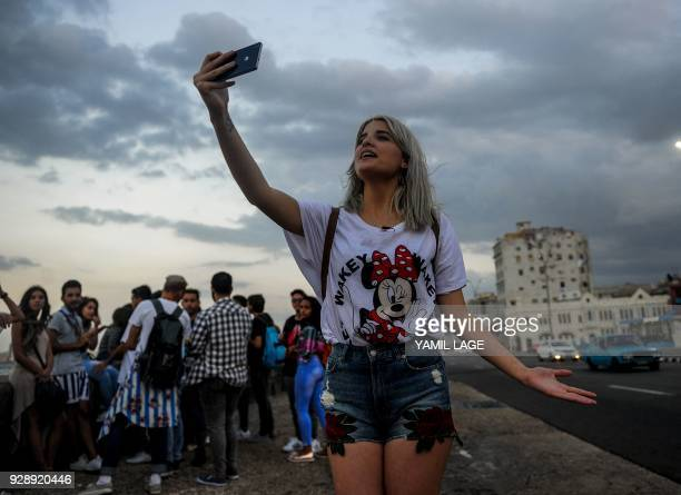 A Cuban youtuber records her youtube program at Havana's Malecon on February 27 2018 Cubans don't have internet access at their homes yet the...
