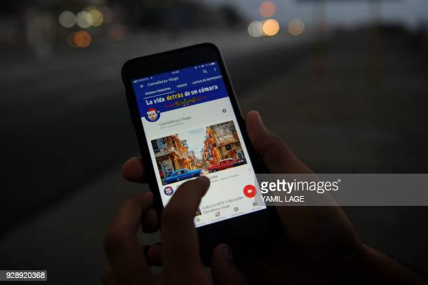 A Cuban youtuber shows her youtube channel on a cellphone at Havana's Malecon on February 27 2018 Cubans don't have internet access at their homes...