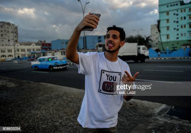 A Cuban youtuber takes a selfie picture at Havana's Malecon on February 27 2018 Cubans don't have internet access at their homes yet the telephone...