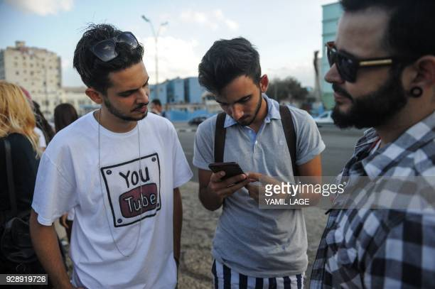 Cuban youtubers check the internet connection in one of them cell phone at Havana Malecon on February 27 2018 Cubans don't have internet access at...