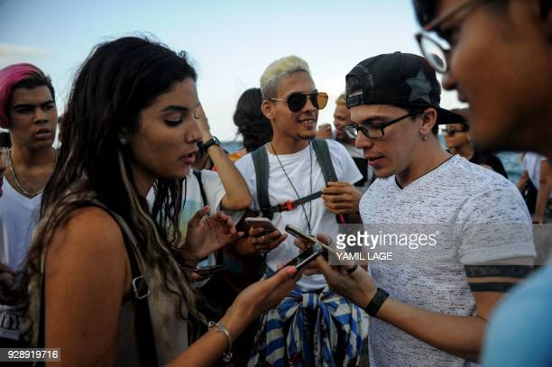 Cuban youtubers check the internet connection in their cell phones at Havana Malecon on February 27 2018 Cubans don't have internet access at their...