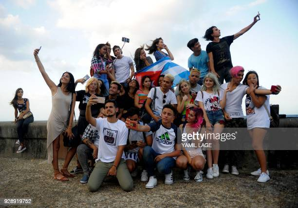 Cuban youtubers take selfies at Havana Malecon on February 27 2018 Cubans don't have internet access at their homes yet the telephone state company...