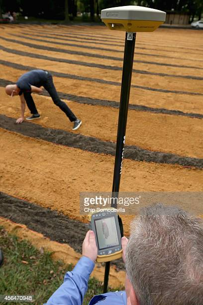 CubanAmerican artist Jorge RodriguezGerada smooths dirt by hand inside his sixacre sand and soil 'facescape' as Topcon Vice President Mark Contino...