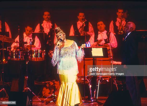 CubanAmerican salsa singer Celia Cruz holds a Cuban flag in her left hand as she performs at the JVC Jazz Festival concert 'Two Divas and a Lion' at...