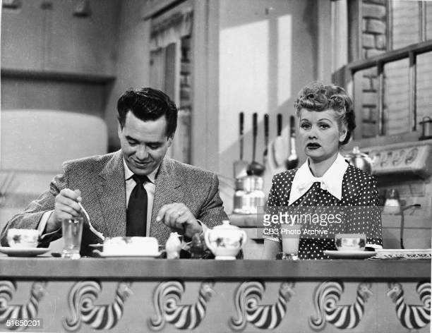 Cuban-born actor Desi Arnaz sits at the kitchen table and eats breakfast alongside his real-life wife American actress and comedienne Lucille Ball in...