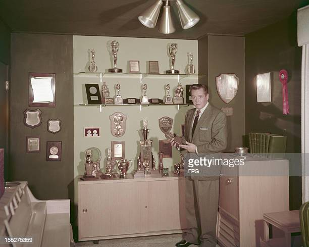 Cuban-born American actor and musician Desi Arnaz with the many awards won by himself, his wife Lucille Ball, and their hit comedy show 'I Love...