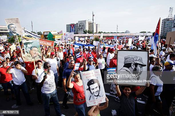 Cubans carry images of Che Guevara and Cuba's Revolution leader Fidel Castro during the annual march of thousands of Cubans celebrating May Day at...