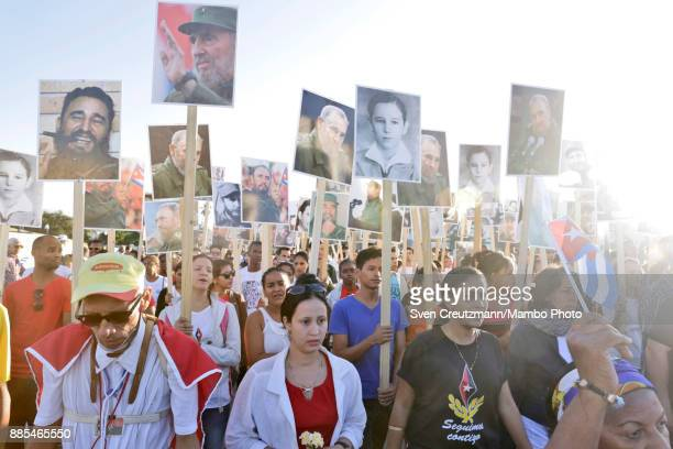 Cubans carry photos of late Cuban Revolution leader Fidel Castro during a march from the Revolution square to the Santa Ifigenia cemetery as Cuba...