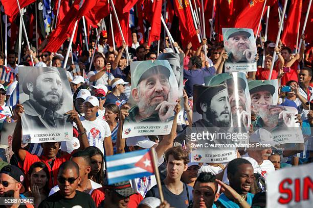 Cubans carry photos of Revolution leader Fidel Castro on occasion of his upcoming 90th birthday in August during a march celebrating workers day at...
