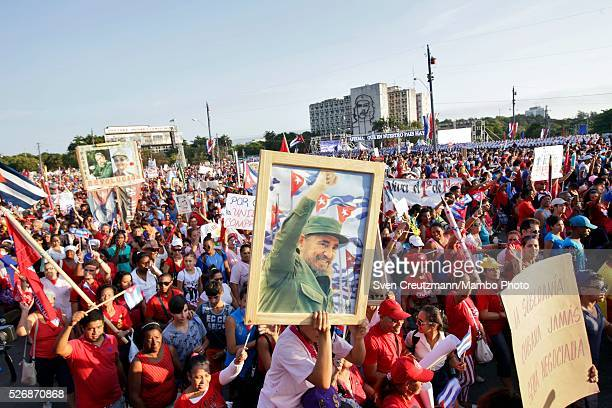 Cubans carry photos of Revolution leader Fidel Castro on occasion of the upcoming 90th birthday of Castro in August during a march celebrating...