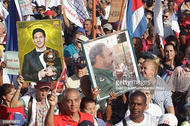 Cubans carry photos of Revolution leader Fidel Castro on the occasion of his upcoming 90th birthday in August next to a photo of soccer player Lionel...