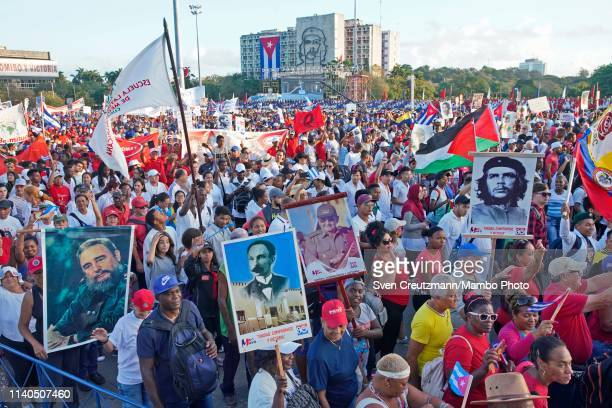 Cubans carry posters and flags with the images of Cuba's late Revolution leader Fidel Castro Head of the Communist Party Raul Castro and Che Guevara...