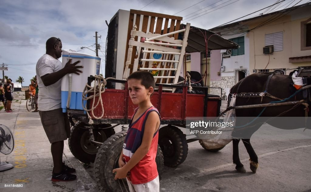 Cubans carry their belongings on September 8, 2017 ahead of the arrival of Hurricane Irma in Caibarien, the only town in the Cuban north central zone under a hurricane warning. Irma, currently a Category Four storm packing 240 kilometre per hour (150 mph), has already left death and destruction in other Caribbean islands. The hurricane has already begun moving between Cuba's north coast and the central Bahamas, and rains and rising winds have begun to be felt in Havana. / AFP PHOTO / Adalberto ROQUE