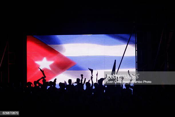 Cubans celebrate in front of a Cuban flag prior to a march celebrating workers day at the Plaza de la Revolucion on May 1 2016 in Havana Cuba Cuba...