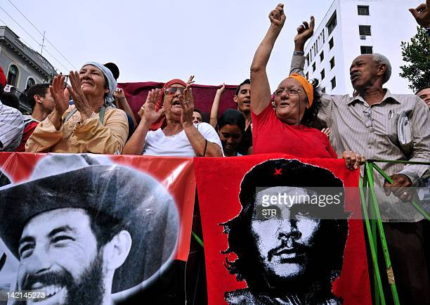 Cubans celebrate with posters of revolutionary leaders Argentinianborn Ernesto Che Guevara and Cuban Camilio Cienfuegos the 49th anniversary of the...