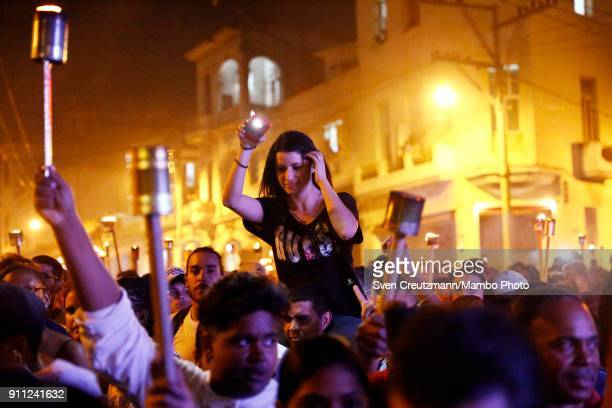 Cubans hold cell phones and torches during a march as Cuba celebrates the 165 anniversary of the birth of its national hero Jose Marti on January 27...