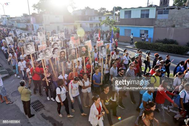 Cubans hold photos of late Cuban Revolution leader Fidel Castro during a march from the Revolution square to the Santa Ifigenia cemetery as Cuba...