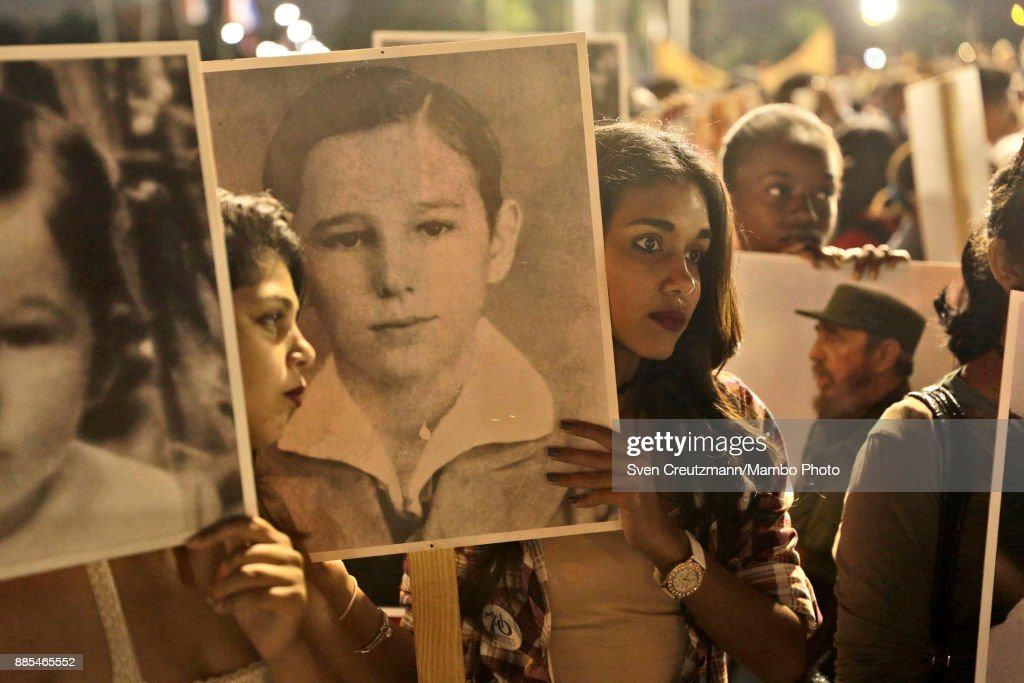Cubans hold photos of late Cuban Revolution leader Fidel Castro at the Revolution square prior to a march towards the cemetery, as Cuba commemorates the first anniversary of Castros funeral, on December 4, 2017 in Santiago de Cuba. Castro died on November 25, 2016 and his remains were buried on December 4th, 2016, after spending one night at the Revolution square, in Santiago de Cuba. Cuba will hold elections in February who will define the successor of Cubas President, Raul Castro.