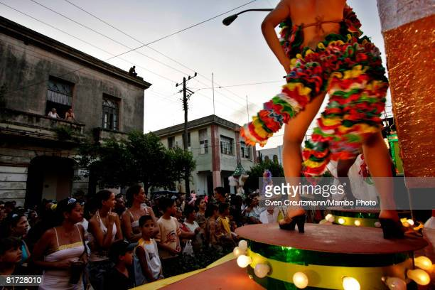Cubans look at a dancer performing during the Camaguey carnival June 25 2008 in Camaguey Cuba The first day celebration of the Camaguey St John...