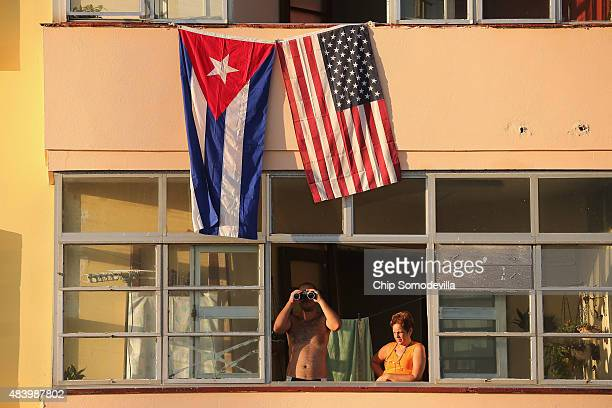 Cubans look out their window across the street from the newly reopened US Embassy in hopes of watching the flagraising ceremony August 14 2015 in...