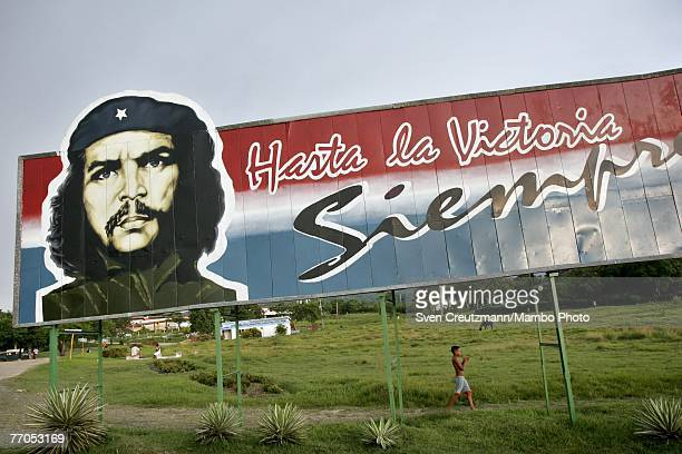 Cubans pass by and kids play under an image of late guerilla fighter Che Guevara September 20 2007 in Biran Cuba The words on the sign read the most...