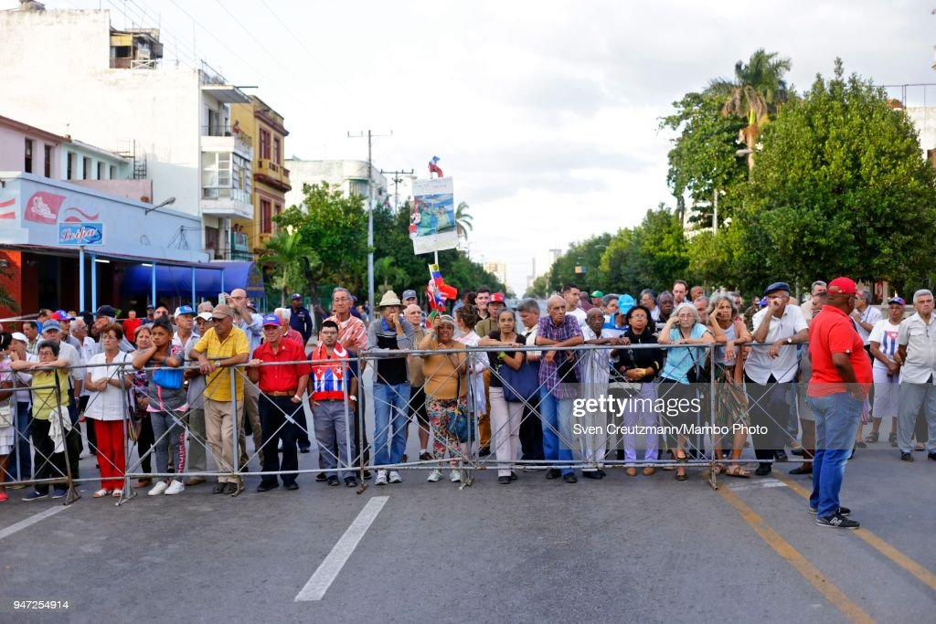 Cubans stand behind a fence while attending a political act commemorating the 57th anniversary of a speech in which Fidel Castro declared the revolution to be Socialistic, on April 16, 2018 in Havana, Cuba. The act took place at the same corner of the streets 23 and 12 in Havanas Vedado district, where Castro in 1961 attended a funeral rally after the bombing of Cuban airports that marked the begin of the Bay of Pigs invasion.