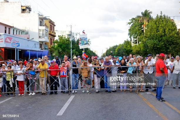 Cubans stand behind a fence while attending a political act commemorating the 57th anniversary of a speech in which Fidel Castro declared the...