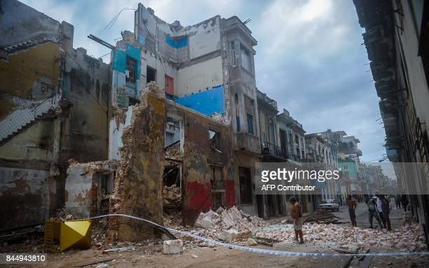 TOPSHOT Cubans stand bt a collapsed building in Havana on September 9 2017 Irma's blast through the Cuban coastline weakened the storm to a Category...