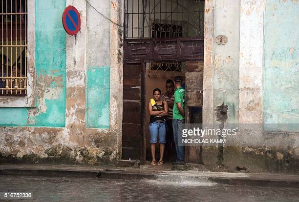 Cubans stand in a doorway hoping to catch a glimpse of US President Barack Obama as he and his family tour Old Havana on March 20 2016 Obama arrived...