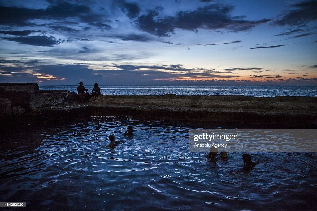 Cubans swim in a coastal pool as the sun sets along the Gulf of Mexico in the Miramar neighborhood of Havana, Cuba on August 14, 2015.
