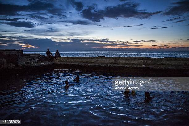 Cubans swim in a coastal pool as the sun sets along the Gulf of Mexico in the Miramar neighborhood of Havana Cuba on August 14 2015